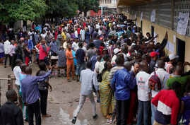 Hundreds of Congolese voters who have been waiting at the St. Raphael school in the Limete district of Kinshasa Sunday Dec. 30, 2018, storm the polling stations after the voters listings were finally posted five hours after the official start of voti