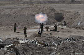 Members of the Iraqi army and Shi'ite fighters launch a mortar toward Islamic State militants on the outskirts of the city of Falluja, Iraq, May 19, 2015.