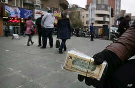 In this picture taken on Monday, Dec. 26, 2016, a street money exchanger holds Iranian and U.S. banknotes in downtown Tehran, Iran. Iran's currency has struck an all-time low this week, trading at 41,600 rials to $1.