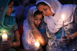 Worshipers in the Sikh community gather for a candle light vigil after prayer services at the Sikh Religious Society of Wisconsin, Monday, Aug. 6, 2012, in Brookfield, Wis.