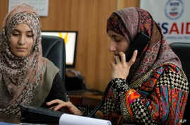 Pakistani lawyer Shandana Naeem, right, listens to a caller with her colleague Nayab Hassan at their office in Peshawar, March 28, 2017.
