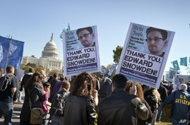 Demonstrators rally at the U.S. Capitol to protest spying on Americans by the National Security Agency, as revealed in leaked information by former NSA contractor Edward Snowden, in Washington, Saturday, October 26, 2013. (AP Photo/J. Scott Applewhit