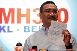 Malaysia's acting Transport Minister Hishammuddin Hussein holds up a note that he has just received on a new lead in the search for the missing Malaysia Airlines Flight MH370, during a news conference at Kuala Lumpur International Airport, Mar. 22, 2