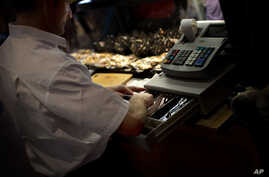 A man uses a cash register at a market in Madrid, Spain, Aug. 13, 2013.