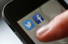 An illustration picture shows a man starting his Twitter App on a mobile device in Hanau near Frankfurt, Oct. 21, 2013.