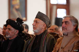 Afghan President Ashraf Ghani, left, former President Hamid Karzai, center, and Chief Executive Abdullah Abdullah, right, attend a ceremony marking the completion of security transition to Afghan security forces in Kabul, Jan. 1, 2015.