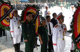 Former Vietnam Communist General Secretary Le Kha Phieu, center, stands between wreaths before paying respects to the late Gen. Vo Nguyen Giap at the National Funeral House in Hanoi, Vietnam, Oct. 12, 2013.