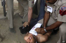 Indian police detain a Tibetan exile participating in an i