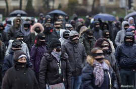 Romanians sporting black cloths over their mouths and eyes protest against the ruling leftist Social Democrat party plans to overhaul judicial legislation in Bucharest, Dec. 17, 2017.