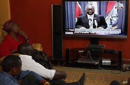 Kenyans watch as the President of the Republic of Kenya, Mwai Kibaki addresses the nation, Friday, March 1, 2013 in Nairobi, Kenya,  ahead of the Monday March 4, 2013 general election.