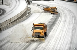 Snow plows clear downtown lanes on Georgia interstate during winter storm, Atlanta, Feb. 12, 2014.