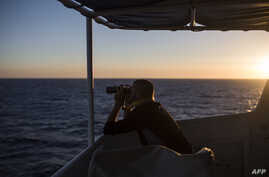 """A member of """"SOS Mediterranee"""", an European association dedicated to search and rescue, uses binoculars during a search operation on the Mediterranean sea, 30 nautical miles from the Libyan coast, July 31, 2017."""