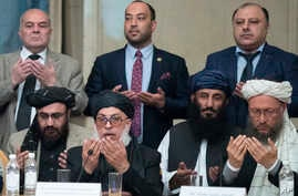 Taliban political chief Sher Muhammad Abbas Stanikzai, in the first row, second from left, Abdul Salam Hanafi and other Taliban officials pray during the intra-Afghan talks in Moscow, Feb. 6, 2019.