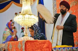 Balbir Singh Pahwa, right, of the Guru Nanak Darbar Sikh house of worship, shows respect for the holy scripture by waving a fan above Satinder Kaur, center, as she leads a prayer recital at the temple, in Hicksville, N.Y. The beards and turbans are s