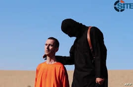 An image grab taken from a video released by the Islamic State (IS) and identified by private terrorism monitor SITE Intelligence Group purportedly shows British aid worker David Haines dressed in orange and on his knees in a desert landscape speakin
