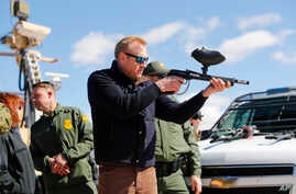 Acting Secretary of Defense Patrick Shanahan, center, fires a modified paint ball gun during a tour of the U.S.-Mexico border at Santa Teresa Station in Sunland Park, N.M., Feb. 23, 2019.