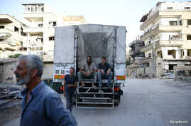 People sit on a Syrian Arab Red Crescent truck, which is part of an aid convoy in the rebel held besieged Harasta area, in the eastern Damascus suburb of Ghouta, Syria, June 19, 2017. Rebel fighters and their families are preparing to leave Harasta f