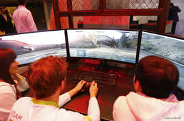 People play a video game on the stand of Acer at the IFA Electronics show in Berlin, Germany, Sept. 2, 2015.