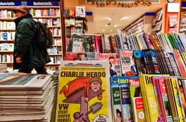 The first issues of the German version of French satirical weekly Charlie Hebdo are for sale at a newsstand in Berlin, Dec. 1, 2016.