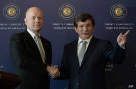 British Foreign Secretary William Hague, left, and his Turkish counterpart Ahmet Davutoglu shake hands after a news conference in Istanbul, Turkey, Nov. 20, 2013.