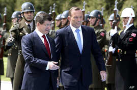 Turkish Prime Minister Ahmet Davutoglu, left, and his Australian counterpart Tony Abbott inspect a military honour guard during a welcome ceremony in Ankara, April 22, 2015.