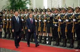 South Korean President Moon Jae-in, center right, and Chinese President Xi Jinping review the Chinese honor guard during a welcoming ceremony at the Great Hall of the People in Beijing, Dec. 14, 2017.