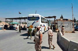 This photo released by the Syrian official news agency SANA, shows Syrian government forces overseeing the evacuation by bus of Army of Islam fighters from the besieged town of Douma, just east of Damascus, Syria, April 2, 2018. (SANA via AP)