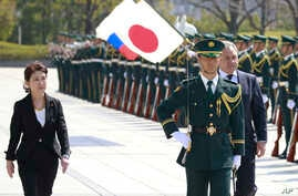 Russian Defense Minister Sergei Shoigu, right, reviews an honor guard with his Japanese counterpart Tomomi Inada upon arrival at Defense Ministry in Tokyo, March 20, 2017.