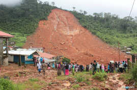People inspect the damage after a mudslide in the mountain town of Regent, Sierra Leone, Aug. 14, 2017.