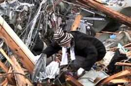 Satoko Kino searches through the remnants of her family home in Ofunato, March 16, 2011