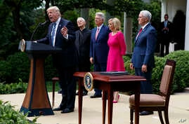 President Donald Trump speaks in the Rose Garden of the White House in Washington before signing an executive order aimed at easing an IRS rule limiting political activity for churches, May 4, 2017. From second from left are Cardinal Donald Wuerl, ar
