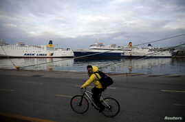 A man rides his bicycle as passengers ships are moored during a 24-hour general strike against planned pension reforms at the port of Piraeus, near Athens, Greece, Feb. 4, 2016.
