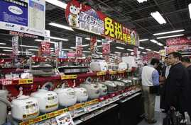 FILE - Chinese customers look at rice cookers in Tokyo's Akihabara electronics district, March 25, 2010. The Chinese government's push to transform itself into a consumer driven economy encourages the production of better consumer appliances.