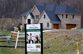 FILE - In this Feb. 27, 2017 photo, real estate signs mark the lots near one of the new homes for sale in a development for new homes in Cranberry Township, Butler County, Pa.