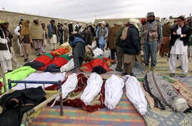 Bodies of victims killed from Sunday's suicide attack are laid on the ground in the Yahyakhail district of Paktika province east of Kabul, Afghanistan, Nov. 24, 2014.