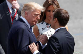 French President Emmanuel Macron shakes hands with U.S. President Donald Trump as first lady Melania Trump looks on after the traditional Bastille Day military parade in Paris, July 14, 2017.