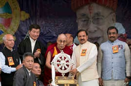 Tibetan spiritual leader the Dalai Lama presents a memento to Junior Indian Culture Minister Mahesh Sharma, second right, as he arrives to attend an event marking the beginning of the 60th year of the Dalai Lama's exile in India, in Dharmsala, India,