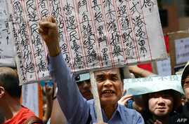 A demonstrator shouts during a protest to denounce the governments voting system outside the venue where a 1,200-member election committee are to choose the city's new leader, in Hong Kong, March 25, 2012.