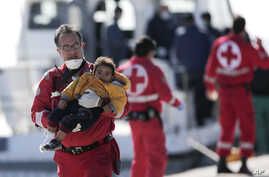 Red Cross volunteer Stavros Zembillis carries a little child just disembarked from a crippled freighter carrying hundreds of refugees trying to migrate to Europe, at the coastal Cretan port of Ierapetra, Greece, Nov. 27, 2014.