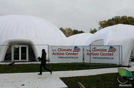 A woman walks past a tent, set up by U.S. groups opposed to U.S. President Donald Trump climate policies, on the sidelines of U.N. COP-23 climate conference in Bonn, Germany, Nov. 9, 2017.