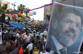 Members of the Muslim Brotherhood and supporters of deposed Egyptian President Mohamed Morsi hold a giant poster as they walk with their families in the sit-in area of Rab'a al- Adawiya Square, Aug. 8, 2013.