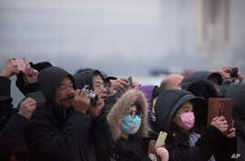 People wearing face masks walk take photos of the daily flag-lowering ceremony at Tiananmen Square on a day with poor air quality in Beijing, Nov. 28, 2015.