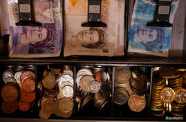 FILE - Pound notes and coins are seen inside a cash register in Manchester, Britain, Sept. 6, 2017. Britain's exit from the European Union's customs union could cost traders dearly.