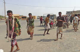 Yemeni fighters loyal to the Saudi-backed Yemeni president walk down a street in the town of Khokha in the western province of Hodeidah on Dec. 18, 2018.