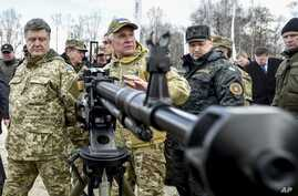 Ukraine's President Petro Poroshenko, left, followed by officials, listens to a weapons expert as he inspects weapon systems for the Ukrainian Army at a military base in Novi Petrivtsi outside Kiev, Ukraine, April 4, 2015.