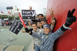 Young Tunisian boys make victory signs during a gathering as part of the festivities marking the second anniversary of the uprising that ousted long-time dictator Zine El Abidine Ben Ali, in Tunis, January 14, 2013.