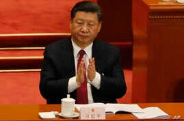 In this March 9, 2018 photo, Chinese President Xi Jinping claps to applaud China's Procurator-General Cao Jianming during a plenary session of China's National People's Congress at the Great Hall of the People in Beijing.