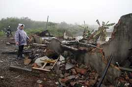 Doan Van Vuon's wife Nguyen Thi Thuong stands by debris of their house after it was destroyed by local authorities and armed forces in Quang Vinh commune, in Vietnam's northern port city of Hai Phong, February 4, 2012.