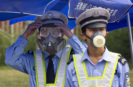 Chinese traffic police wear masks as they man a security checkpoint near the site of an explosion in northeastern China's Tianjin municipality, Aug. 15, 2015.