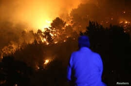 A man observes wildfire in the village of Mravince near Split, Croatia, July 17, 2017.